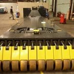 Nákladní plošina s dálkovým ovládáním vybavená speciálními koly pro snížení tlaku na povrch podlahy při přepravě těžkých nákladů. Nosnost do 80 tun.
